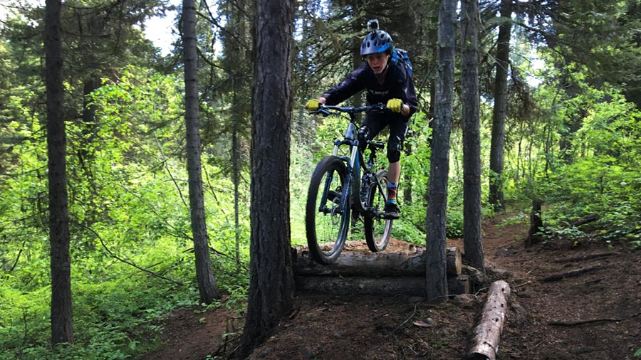 Jumping a feature on Baby Bear - a mountain biking trail near McCall, Idaho