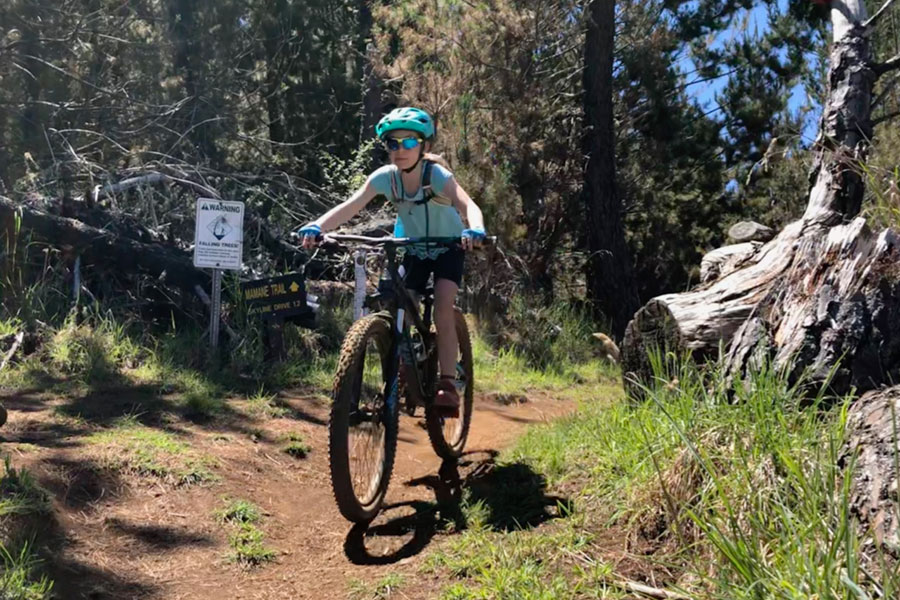 Young girl mountain biking in Maui with family