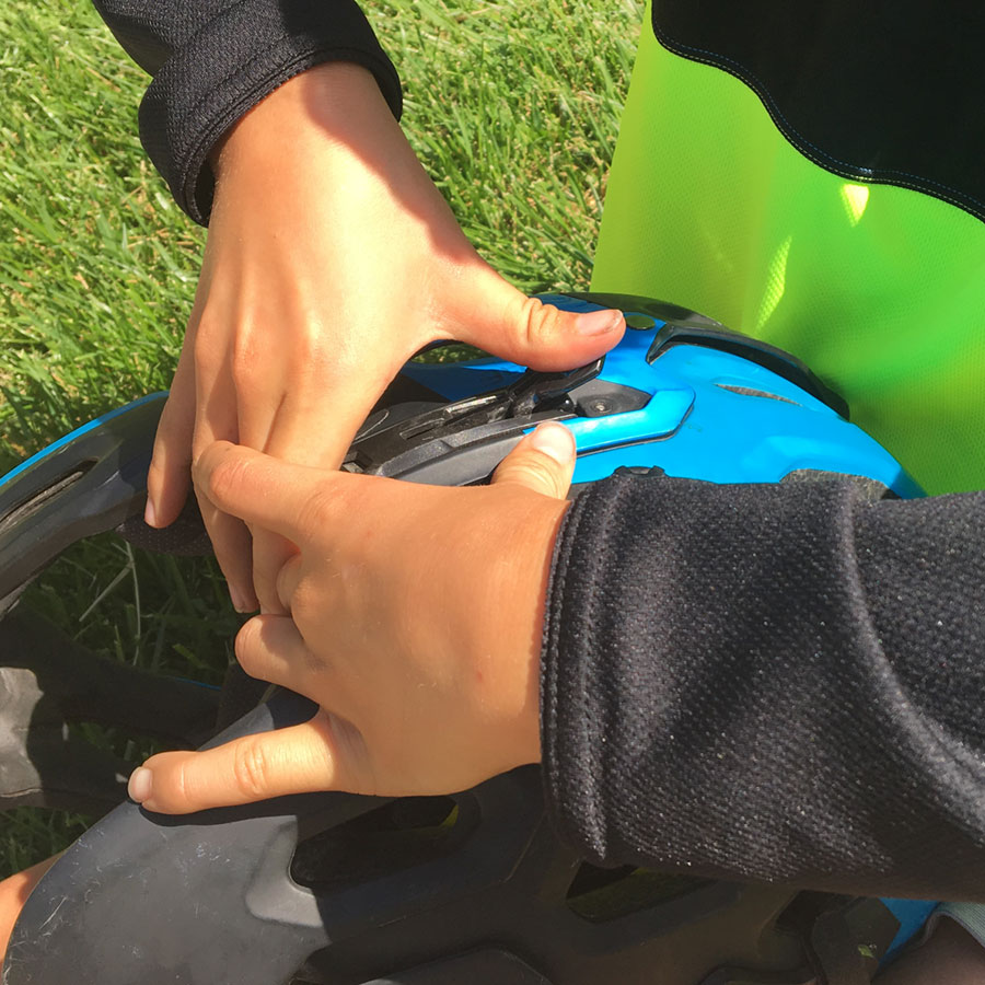 10-year old fastening the side clasp of a Bell Super 2r chin bar- mountain biking with kids