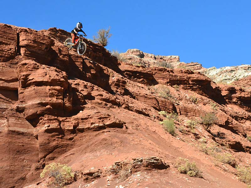A young mountain biker doing a large step-down