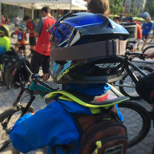 Young mountain biker wearing the Leatt DBX 5.5 Junior neck brace with hydration pack