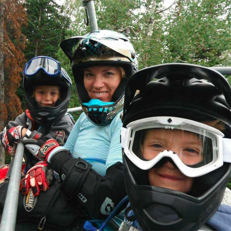 Liz and the kids riding the lift at a bike park
