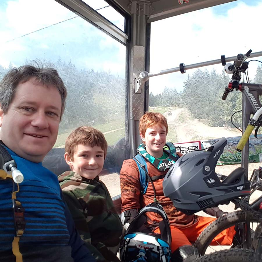 Father and sons riding a gondola at a mountain bike park