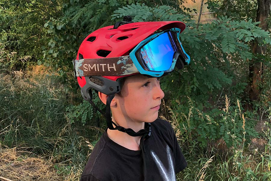 The Bell Super 3r with MIPS mountain bike helmet. Profile view with goggles raised.