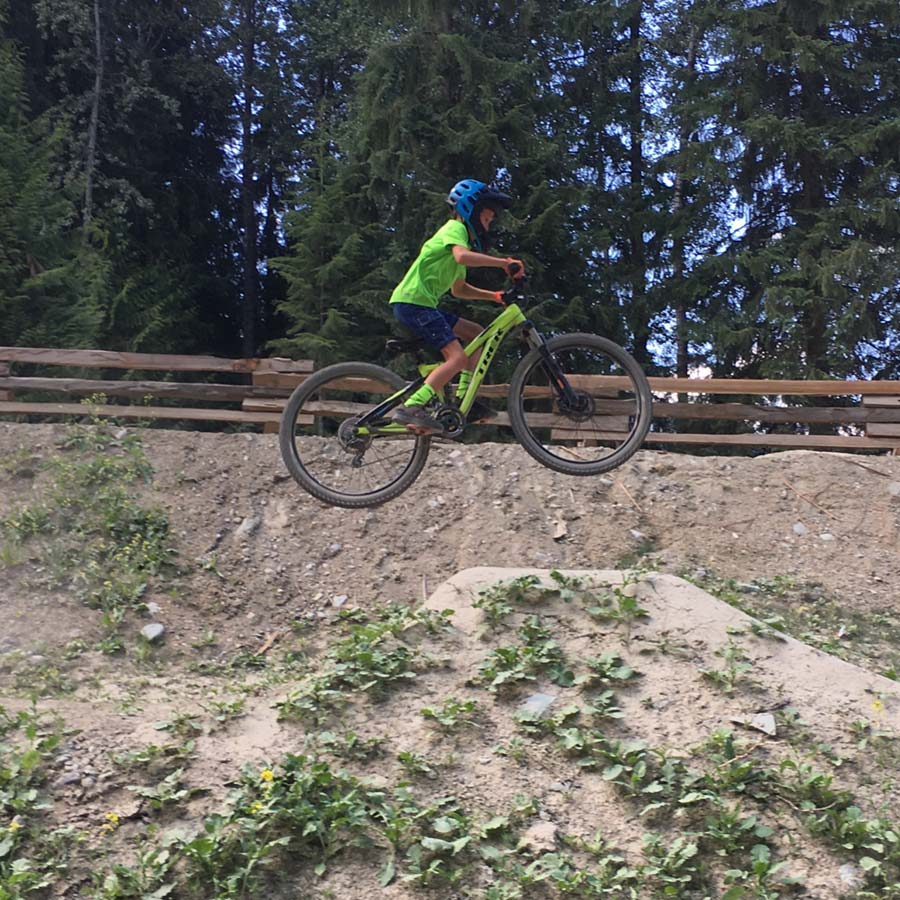 Mountain biking kid on the intermediate dirt jump line -Whistler, BC