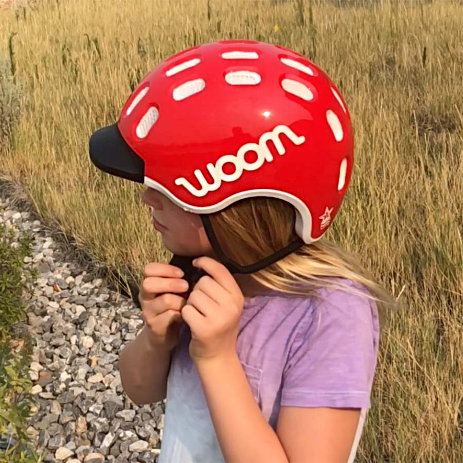 Fastening the magnetic Fidlock magnetic clasp on the Woom bike helmet is a cinch - not a pinch
