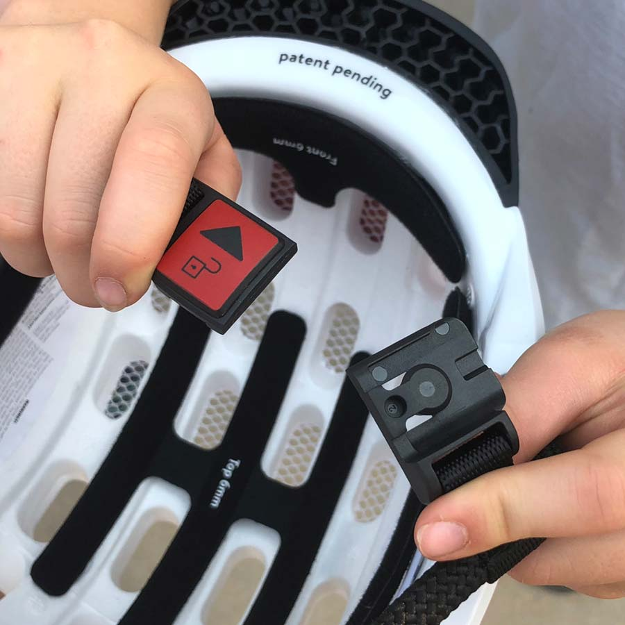 Detail view of the magnetic chin strap clasp on the Woom Kids Helmet