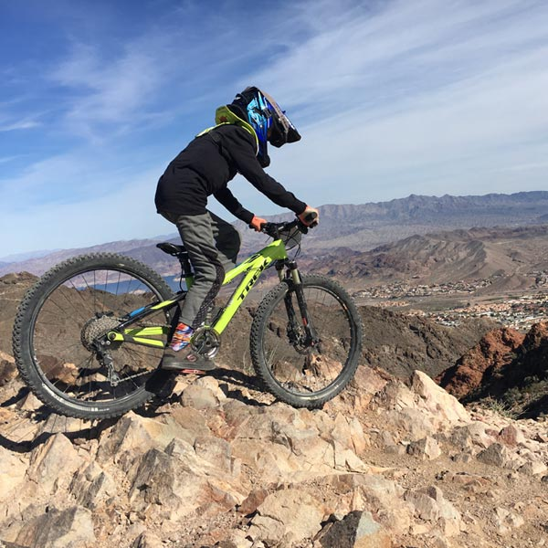 Kid with protective neck brace on downhill mountain bike trail - Bootleg Canyon