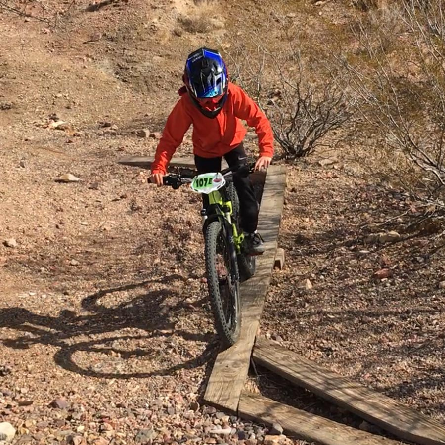 Mountain biking kid on wood skinny