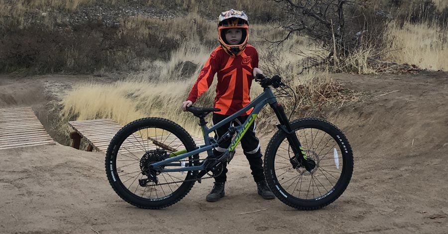 Male youth and the Norco Fluid FS 1 24 full-suspension mountain bike