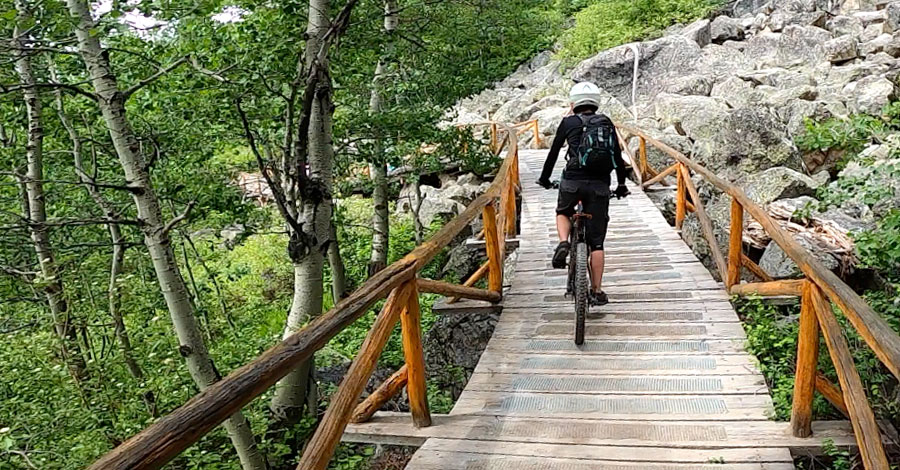 Mom riding a beautiful bridge at the Jackson Hole Bike Park