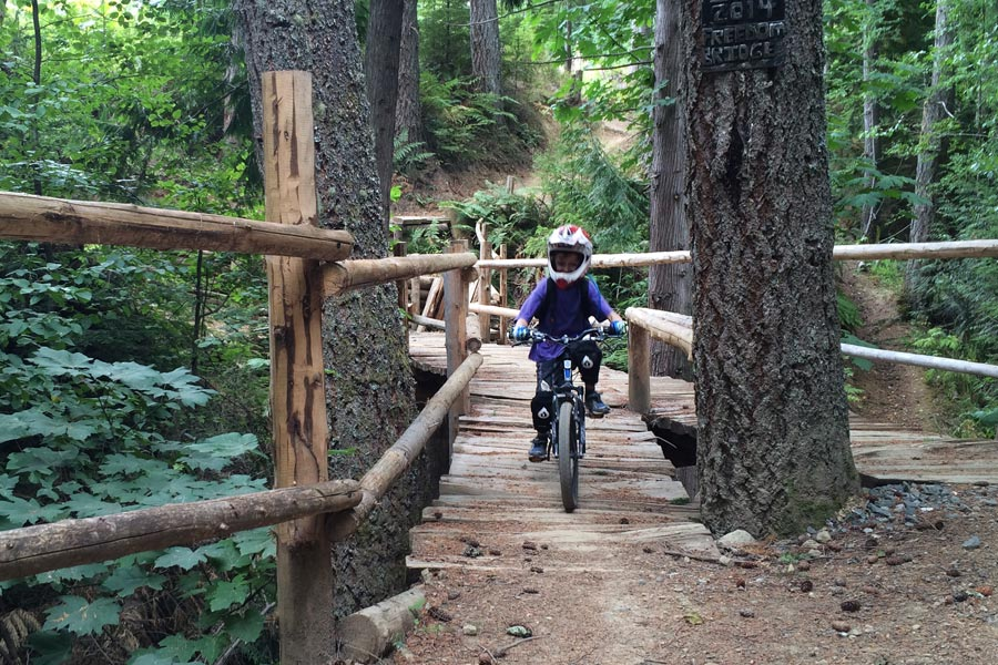Crossing a bridge on Galbraith Mountain's beginner / family-friendly mountain bike trails